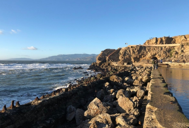 Front edge of the Sutro Baths seen from southwest edge of the ruins. Ocean surf seen at left is held back by a wall studded with stumps of rusty steel bars. Rubble has been filled in between that and a wall with a flat top about 18 inches wide on which people are walking in the distance. The inner wall holds in an extensive pond, seen to the right. Cliffs ahead, headlands in the distance.